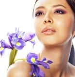 A mulher asiática bonita nova com fim flor-de-luce roxo da flor isolou acima termas, conceito do dia da mulher Fotografia de Stock
