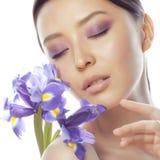 Mulher asiática bonita nova com fim roxo da orquídea da flor isolada acima nos termas brancos do fundo, conceito dos cuidados méd Imagem de Stock