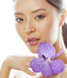 Mulher asiática bonita nova com fim roxo da orquídea da flor isolada acima nos termas brancos do fundo, conceito dos cuidados méd Fotos de Stock