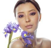 Mulher asiática bonita nova com fim roxo da orquídea da flor isolada acima nos termas brancos do fundo, conceito dos cuidados méd Fotos de Stock Royalty Free