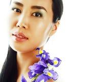 Mulher asiática bonita nova com fim roxo da orquídea da flor acima do isolador foto de stock
