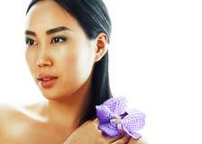 Mulher asiática bonita nova com fim roxo da orquídea da flor acima do isolador imagens de stock royalty free