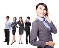Mulher asiática bonita nova no telefone com equipe Foto de Stock Royalty Free