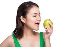 Mulher asiática bonita nova que come a maçã verde fresca nos vagabundos brancos Fotos de Stock