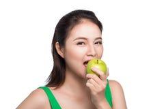 Mulher asiática bonita nova que come a maçã verde fresca nos vagabundos brancos Fotos de Stock Royalty Free