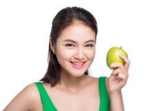 Mulher asiática bonita nova que come a maçã verde fresca nos vagabundos brancos Foto de Stock Royalty Free