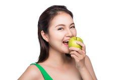 Mulher asiática bonita nova que come a maçã verde fresca nos vagabundos brancos Fotografia de Stock Royalty Free