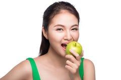 Mulher asiática bonita nova que come a maçã verde fresca nos vagabundos brancos Imagem de Stock