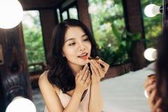 Mulher asiática bonita nova que faz a composição na frente do espelho fotografia de stock