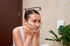 Mulher asiática bonita nova que lava sua cara com mãos pelo sabão foto de stock