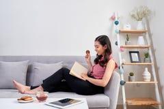 Mulher asiática bonita nova que senta-se no sofá que lê um enjo do livro fotografia de stock