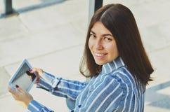 Mulher asiática bonita nova que sorri na câmera e que guarda uma tabuleta em suas mãos imagens de stock