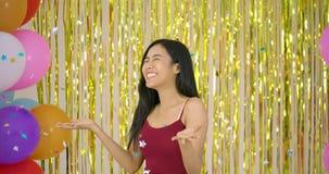 Mulher asiática bonita para apreciar com confetes sobre o fundo do brilho do ouro filme