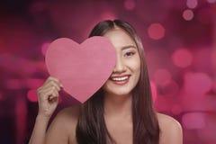 Mulher asiática bonita que cobre seu olho com o símbolo vermelho do coração Fotografia de Stock