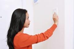 Mulher asiática bonita que desliga a luz com o interruptor da parede imagem de stock