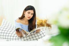 A mulher asiática bonita que encontra-se na cama acolhedor branca que lê um livro aprecia do resto na casa do conforto imagens de stock royalty free