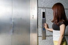 Mulher asiática bonita que está pelo elevador foto de stock royalty free