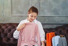 Mulher asiática bonita que senta-se no sofá imagem de stock