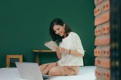 Mulher asiática bonita que usa o laptop na cama na sala e no smil imagens de stock