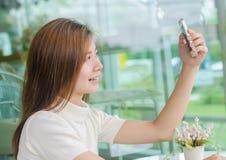 Mulher asiática bonita que usa um smartphone Fotos de Stock Royalty Free