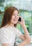 Mulher asiática bonita que usa um smartphone Fotografia de Stock