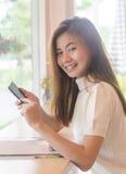 Mulher asiática bonita que usa um smartphone Foto de Stock Royalty Free