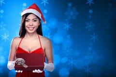 Mulher asiática bonita que veste o traje de Papai Noel que guarda a caixa de presente Fotografia de Stock Royalty Free