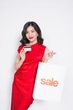 Mulher asiática bonita que veste um vestido vermelho com saco de compras e Fotografia de Stock