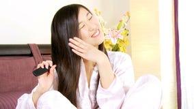 Mulher asiática bonito que escova o cabelo longo de seda em casa vídeos de arquivo