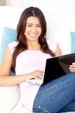 Mulher asiática brilhante que usa seu portátil em casa Fotografia de Stock Royalty Free