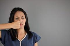 A mulher asiática cheira algo imagem de stock