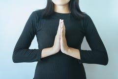 A mulher asiática com mão em rezar a posição da adoração, as mãos fêmeas da oração abraçou junto fotografia de stock