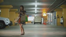 Mulher asiática com os sacos de compras que estão no estacionamento e que usam o smartphone para pedir um táxi video estoque