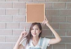 Mulher asiática com placa da cortiça à disposição imagens de stock royalty free