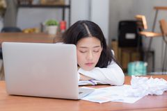 A mulher asiática com sobrecarregado cansado e o sono, menina têm o descanso quando a nota da escrita do trabalho, imagem de stock royalty free