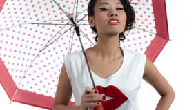 Mulher asiática com um guarda-chuva com o teste padrão de às bolinhas que levanta no estúdio filme