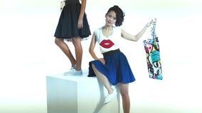 Mulher asiática com um saco colorido que levanta no estúdio A menina preta com às bolinhas ensaca a posição no cubo branco video estoque