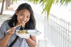 A mulher asiática come o alimento burmese típico em uma rua Imagens de Stock