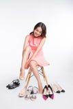 Mulher asiática consideravelmente nova que tenta em alguns pares de saltos altos foto de stock royalty free