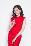 Mulher asiática de comemoração nova no vestido vermelho que guarda o vidro de vinho imagem de stock