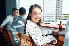 Mulher asiática de sorriso com cerveja no contador imagem de stock
