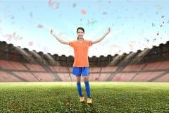 A mulher asiática de sorriso do jogador de futebol comemora a vitória Fotografia de Stock