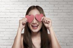 Mulher asiática de sorriso que cobre seu olho com o coração Imagens de Stock Royalty Free