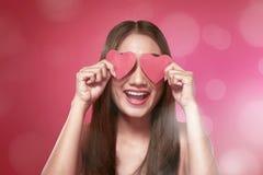 Mulher asiática de sorriso que cobre seus olhos com a forma vermelha do coração Fotografia de Stock