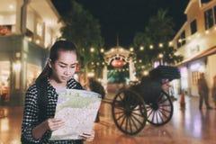 Mulher asiática de viagem com trouxa e vista do mapa na cidade em d imagem de stock royalty free