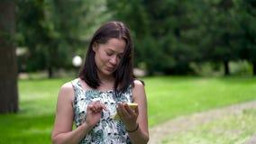 A mulher asiática de vista feliz anda no parque e na conversa em redes sociais filme