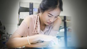 A mulher asiática do adolescente lê e toques em um dispositivo da tabuleta no Foto de Stock