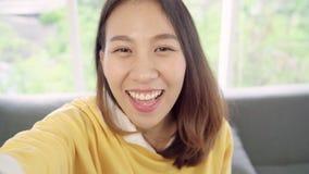 A mulher asiática do blogger que usa o vídeo de gravação do vlog do smartphone na sala de visitas em casa, fêmea aprecia o moment filme