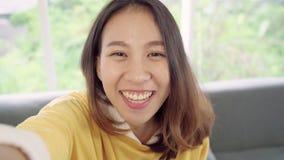 Mulher asiática do blogger que usa o vídeo de gravação do vlog do smartphone na sala de visitas em casa filme