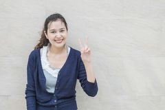 A mulher asiática do close up sustenta um movimento de dois dedos com a cara do sorriso no fundo textured de mármore da parede de imagens de stock